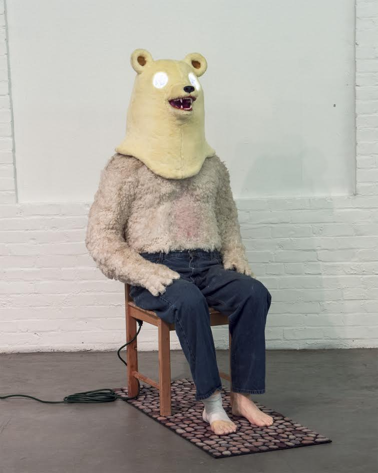 "Raina Belleau, ""The Oracle"", 2016, Acrylic paint, apoxie sculpt, bandage, chair, doormat, electrical components, extension cord, faux fur, jeans, LEDs, mirror, paper mache, plaster and spray paint (Note: This sculpture involves electronic components and lights. The interior of the bear mask is mirrored and LED lights flash, change color and rotate within it.) 60 x 24 x 42in   http://www.rainabelleau.com/"
