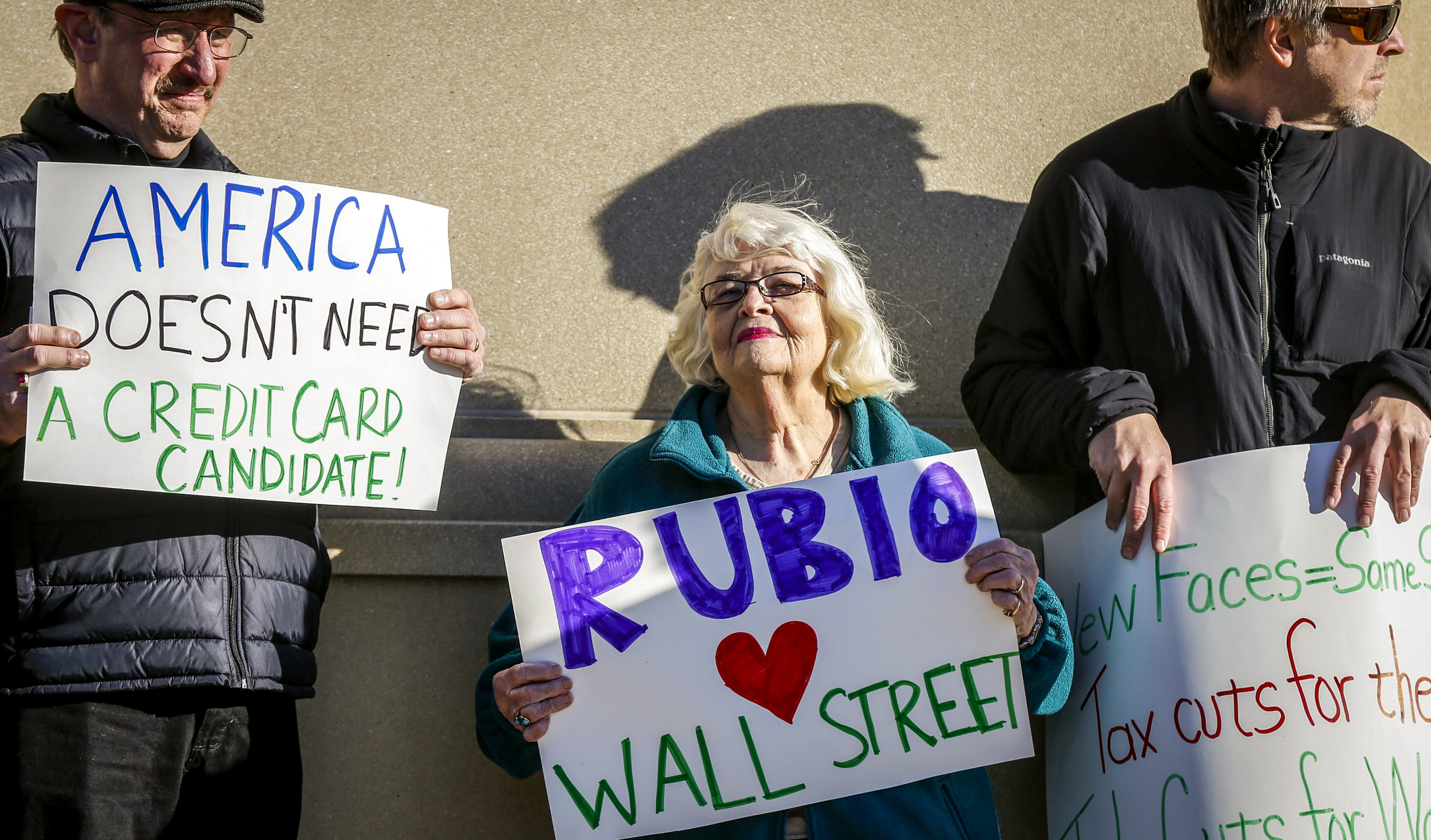 Mary Larew of Iowa City, Iowa, holds a sign in protest of Sen. Marco Rubio outside the Mediacom Outdoor Club in Kinnick Stadium in Iowa City, Iowa, Thursday, Dec. 10, 2015. The republican presidential hopeful made a stop in Iowa City for a meet and greet after visiting Des Moines and Ames earlier in the day.