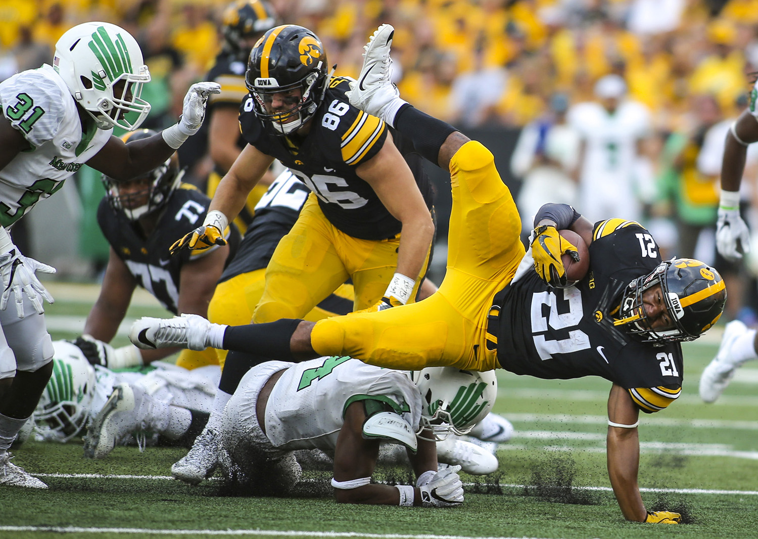 Iowa Hawkeyes running back Ivory Kelly-Martin (21) dives over North Texas safety Khairi Muhammad (4) during the fourth quarter of their game at Kinnick Stadium in Iowa City, Iowa, on Saturday, September 16, 2017.