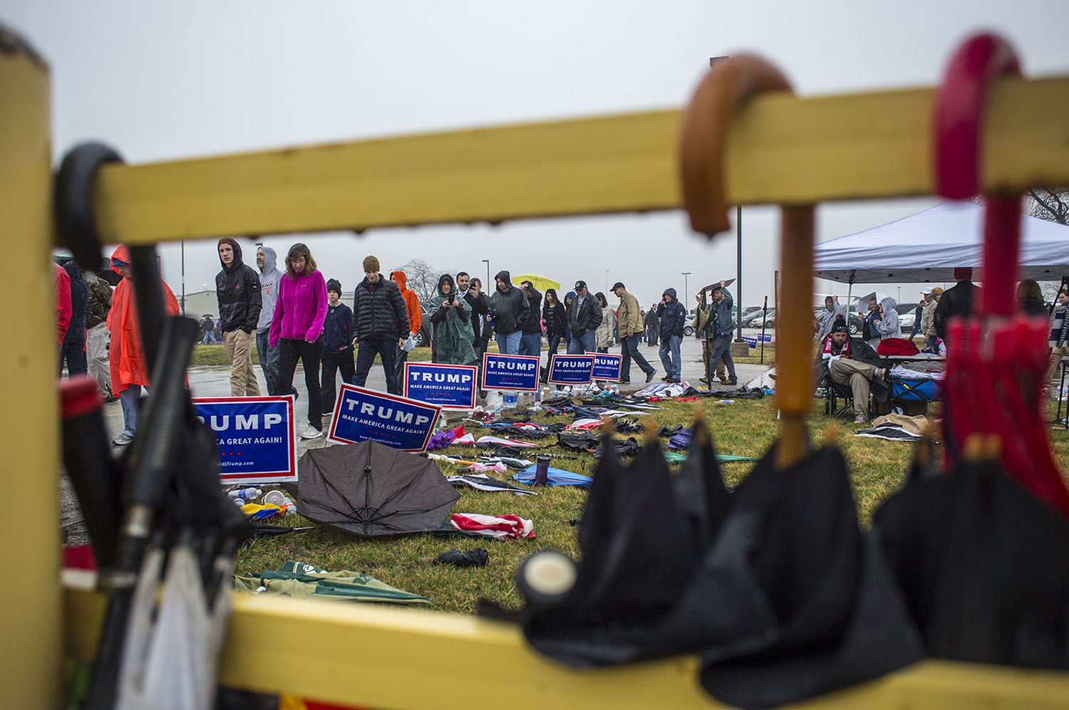 Donald Trump rally attendees wait in line next to a collection of discarded drinks, umbrellas, signs, and other items not to be allowed into the rally at the Synergy Flight Center in Bloomington, Illinois, Sunday, March, 12, 2016.