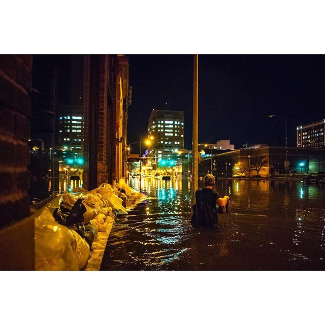 Half Nelson chef Zach Donovan walks through floodwaters down the sidewalk on East 2nd Street leaving the night shift of watching after pumps to go and get some sleep in Davenport, Saturday, May 4, 2019. A mixed crew of owners, chefs, brewers and family friends had been working around the clock since Tuesday to monitor pumps keeping water out of the first level of The Half Nelson and Bootleg Hill Honey Meads. The night shift took turns sleeping while at least two people remained awake at all times in their efforts to save the building. #photojournalism #floodcoverage #flood2019 #mississippiriver #tagthequadcities #qclife