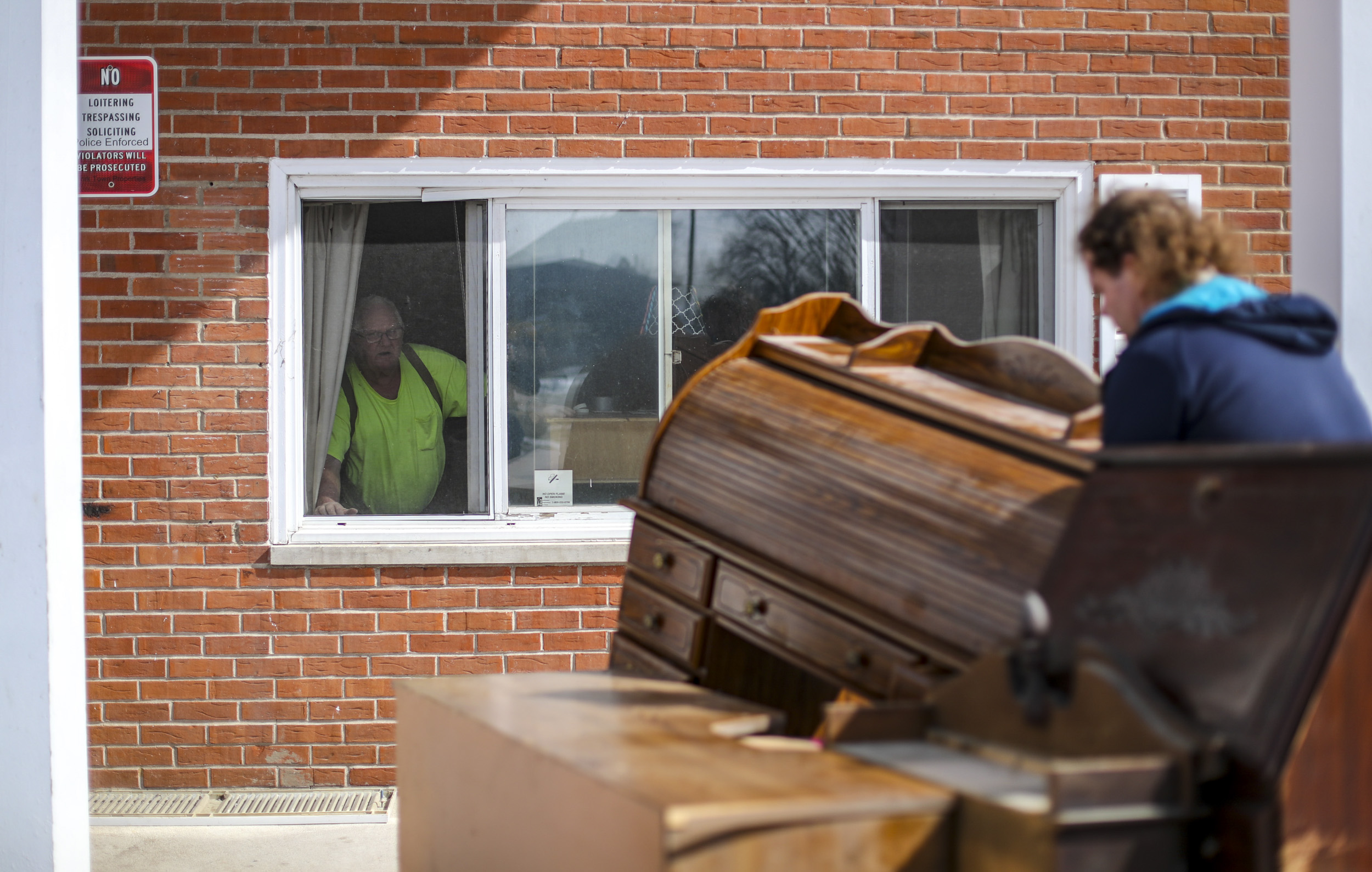 Charles Ray, left, yells to his son, John Ray, as the younger Ray moves a desk onto a trailer in Davenport, Wednesday, March 6, 2019. The elder Ray was forced to leave his apartment of 16 years by March 8 under an order by the city of Davenport.