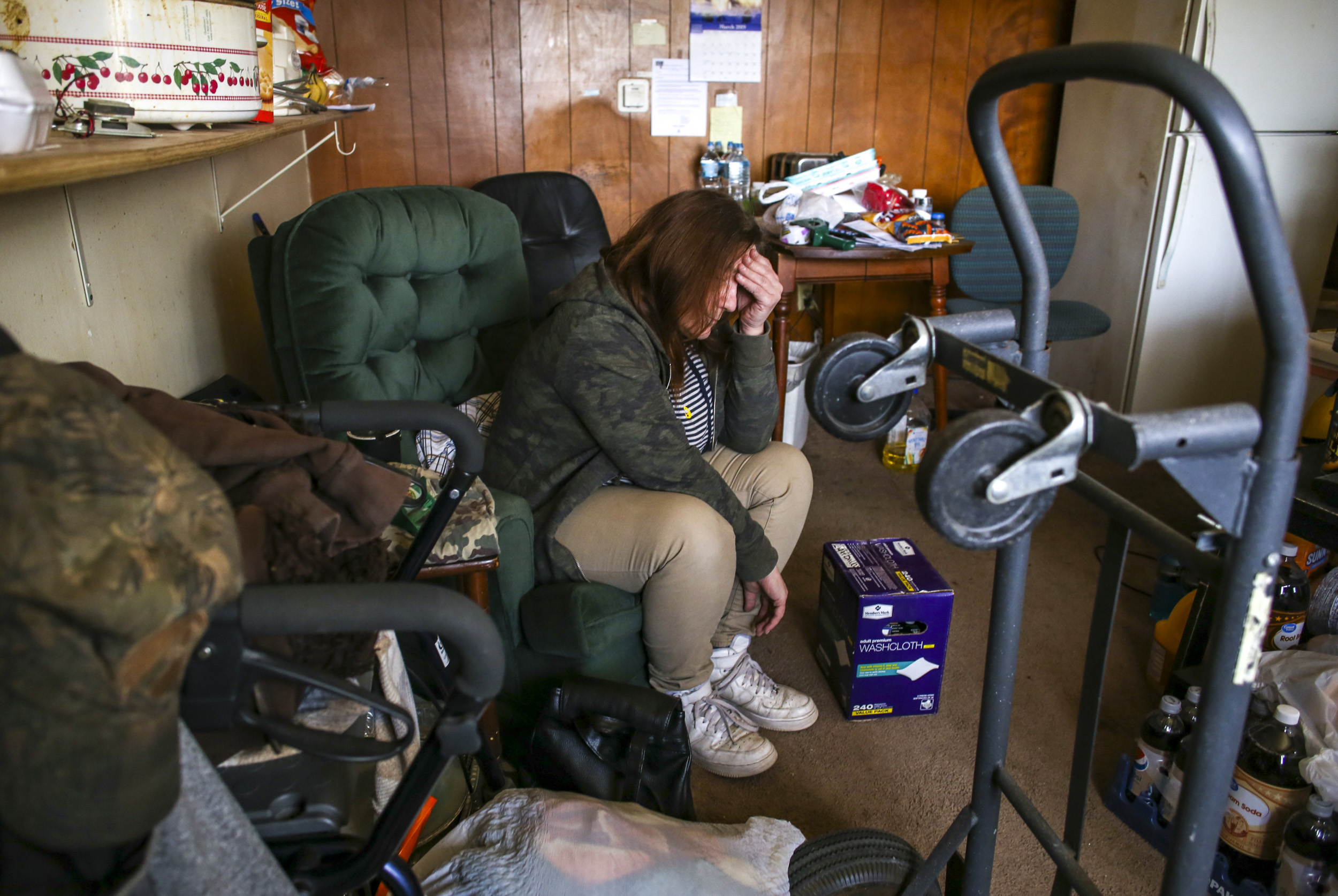 Rebecca Gohn, rests her head in her hand while taking a break from packing up her boyfriend's father's apartment in Davenport, Wednesday, March 6, 2019.