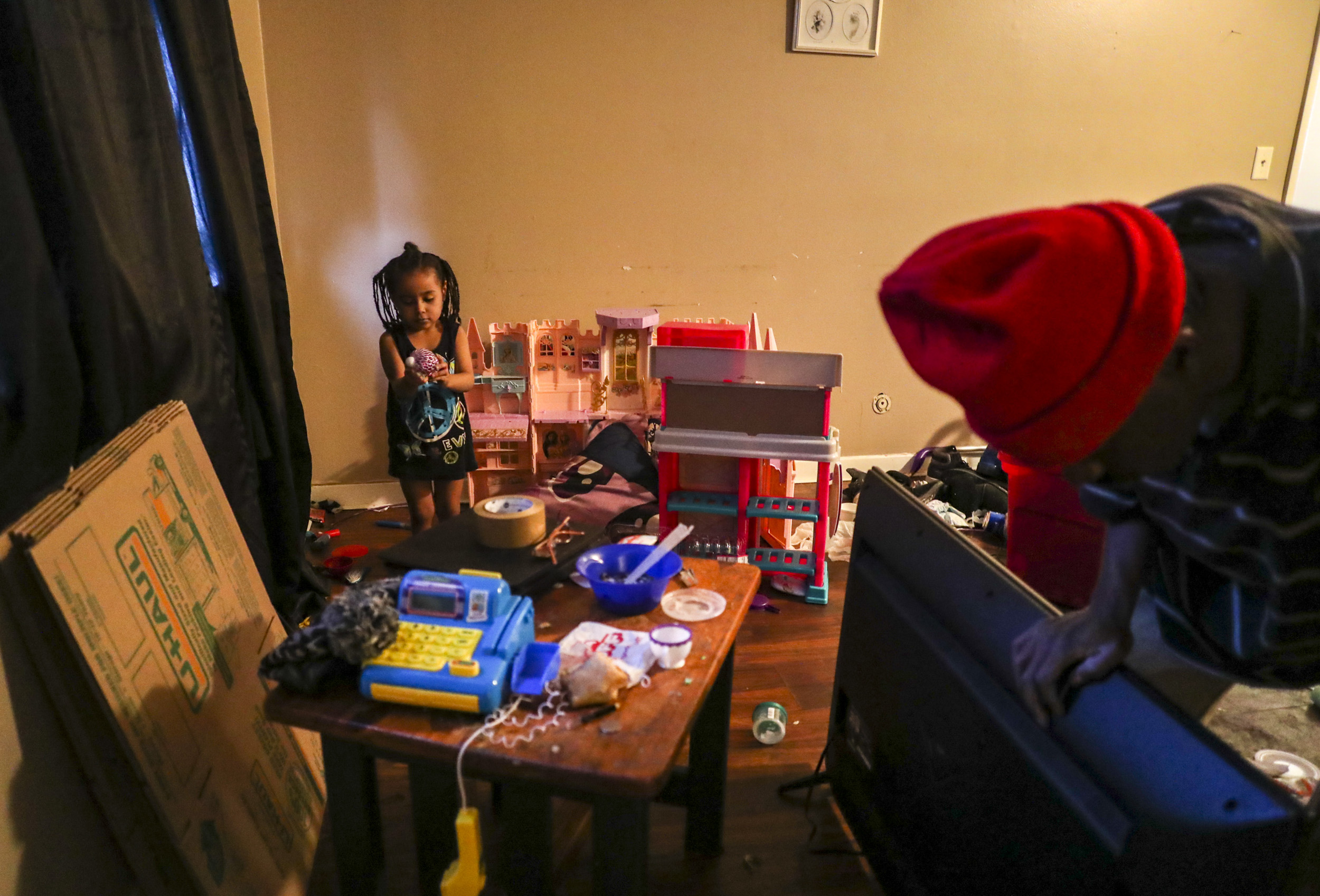 Serenity Thomas-Alonzo, 3, plays as her father, Terrill Thomas, packs up a flatscreen TV to move out to a rental truck in Davenport, Thursday, March 7, 2019. The building they lived in was shuttered by the city of Davenport on Friday, March 8 as a part of an ongoing bankruptcy case that concerns scores of rental properties across the Quad-Cities.