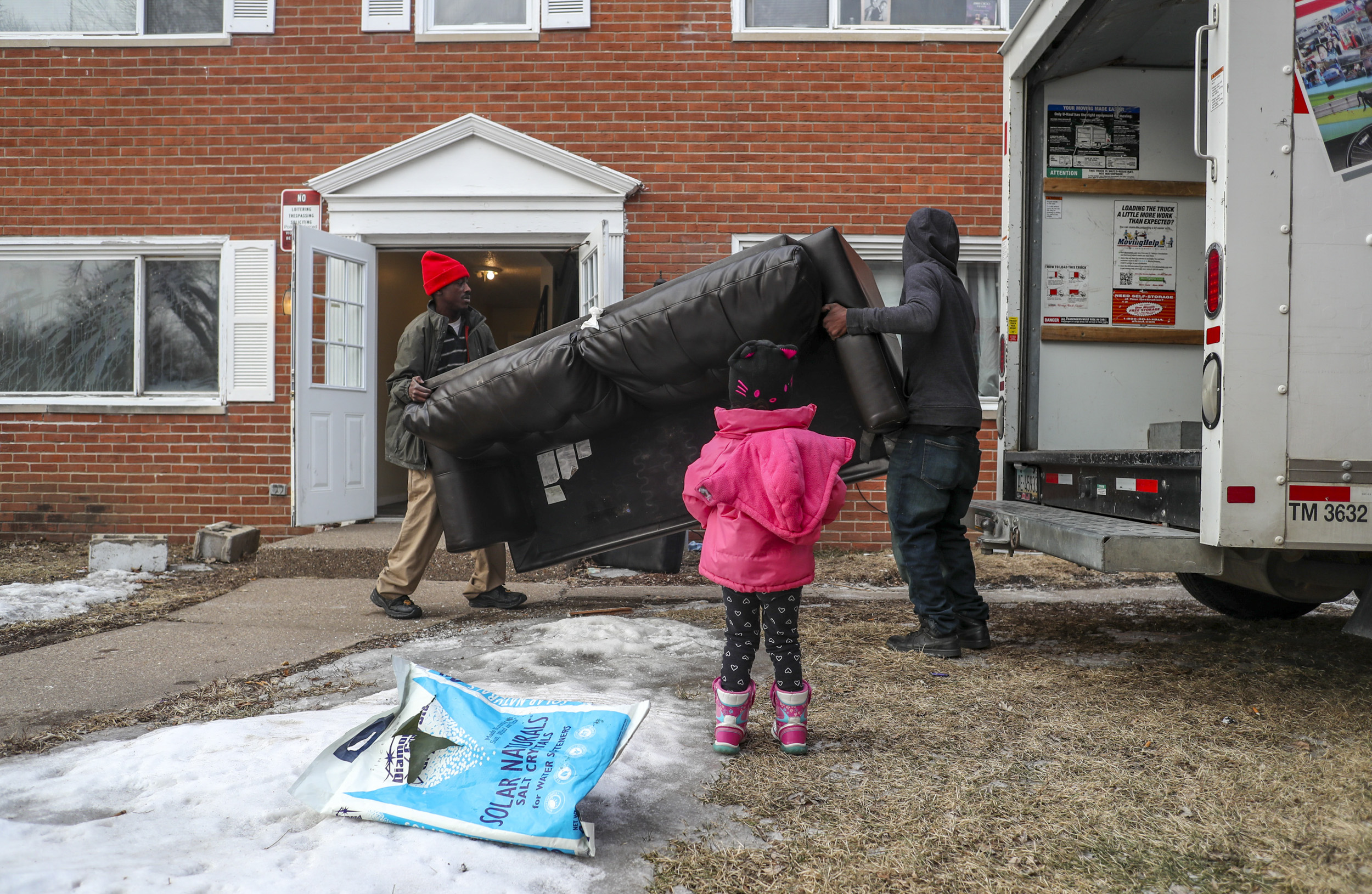 A young girl stands by as Terrill, left, and Andrew Thomas move a sofa into a rental truck in Davenport, Thursday, March 7, 2019. The building Terrill Thomas lived in with his wife and two children was shuttered by the city of Davenport on Friday, March 8.
