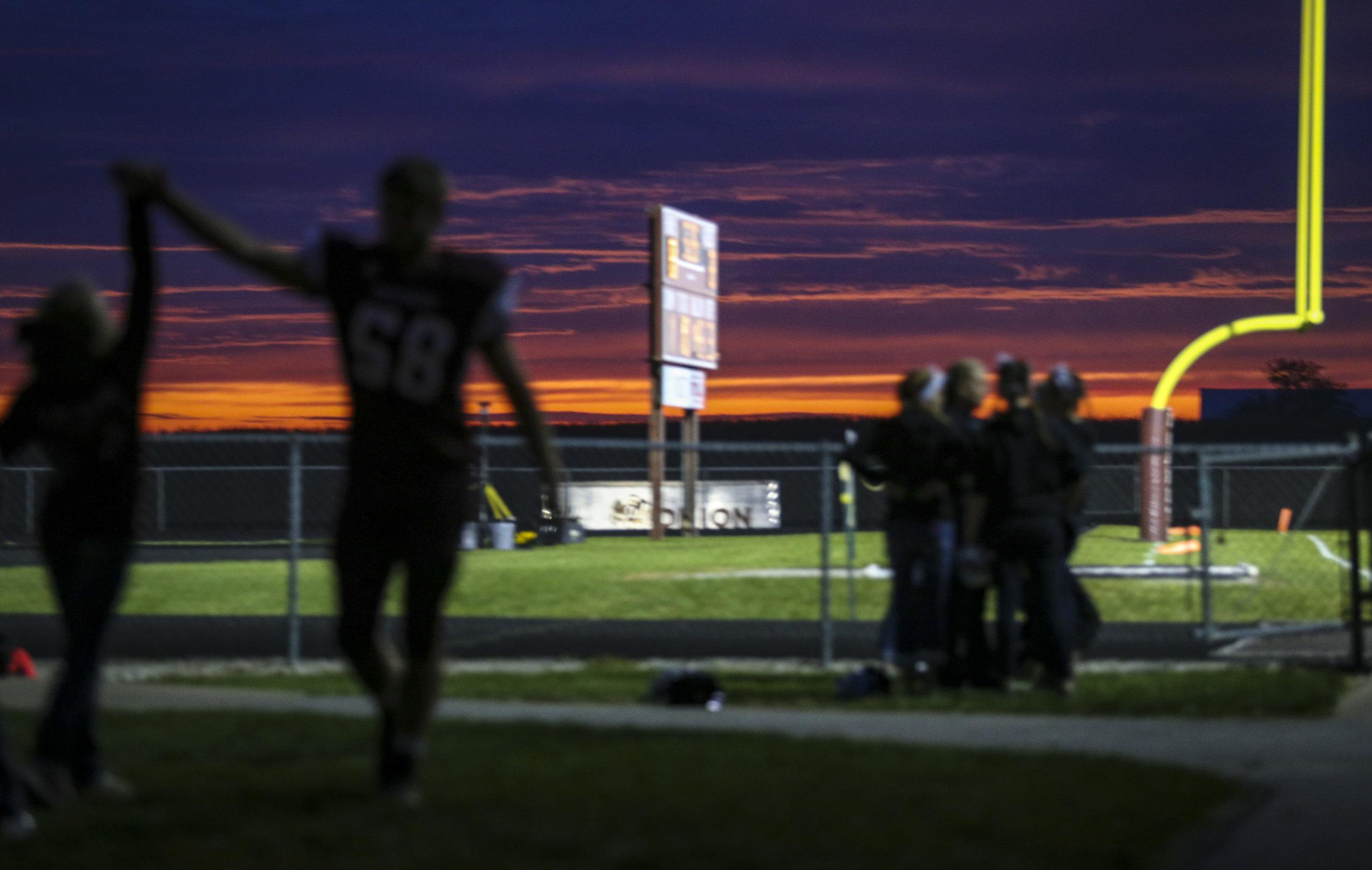 Rockridge's Logan Dierikx (58) gives a high-five while walking toward the locker room before their game at Rockridge High School in Edginton, Friday, October 20, 2017.