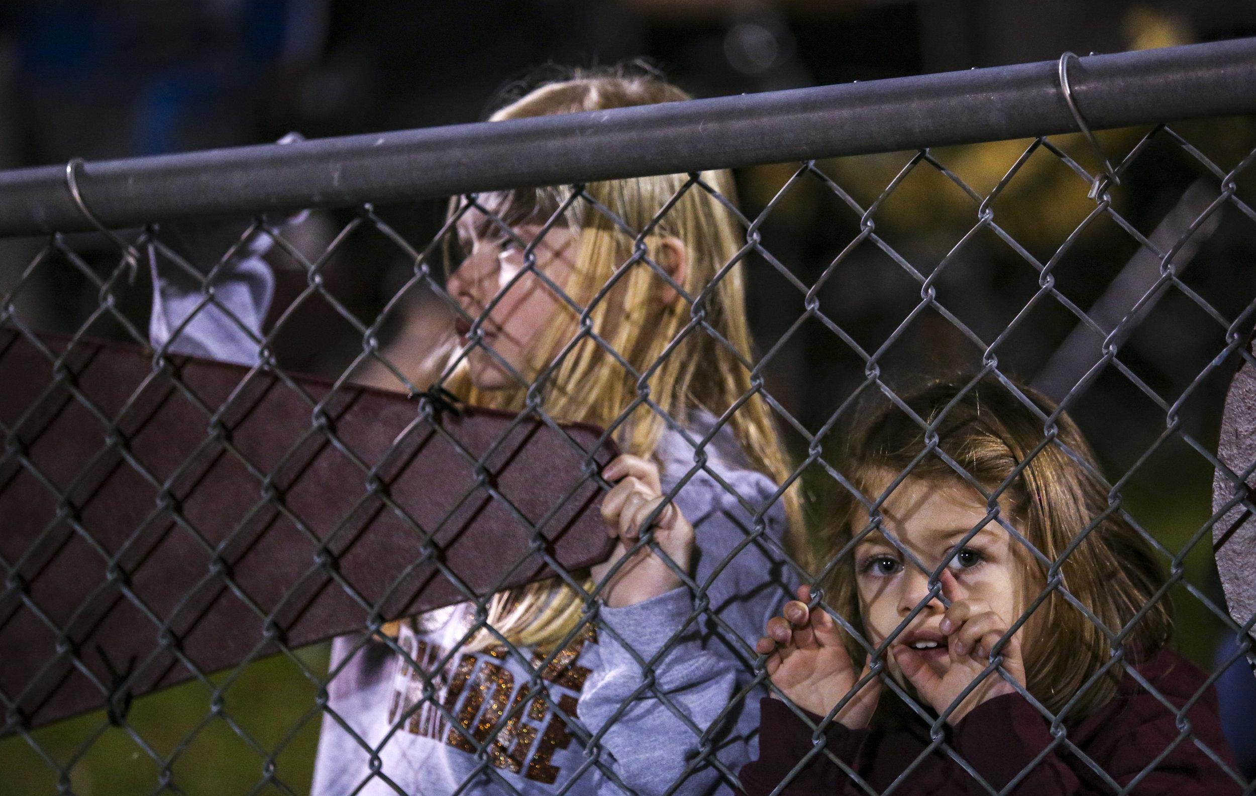 Zoe, 4, and Addison Clarke, 7, of Taylor Ridge watch senior night ceremonies before the varsity football game at Rockridge High School in Edginton, Friday, October 20, 2017.