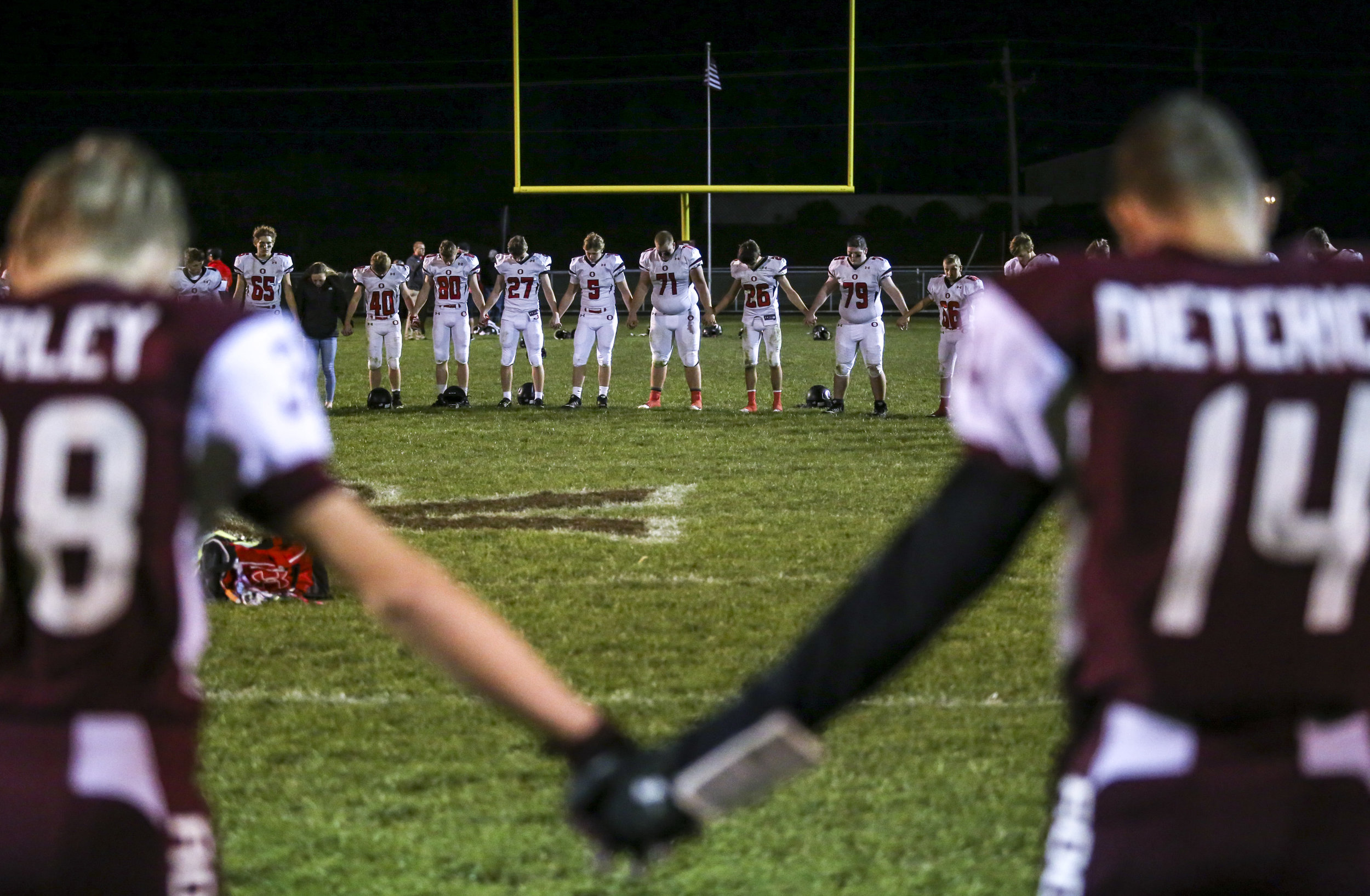 Rockridge players, cheerleaders and fans form a circle with Orion players to say a prayer after their game at Rockridge High School in Edginton, Friday, October 20, 2017. No. 6 Rockridge defeated No. 8 Orion. 20-17.