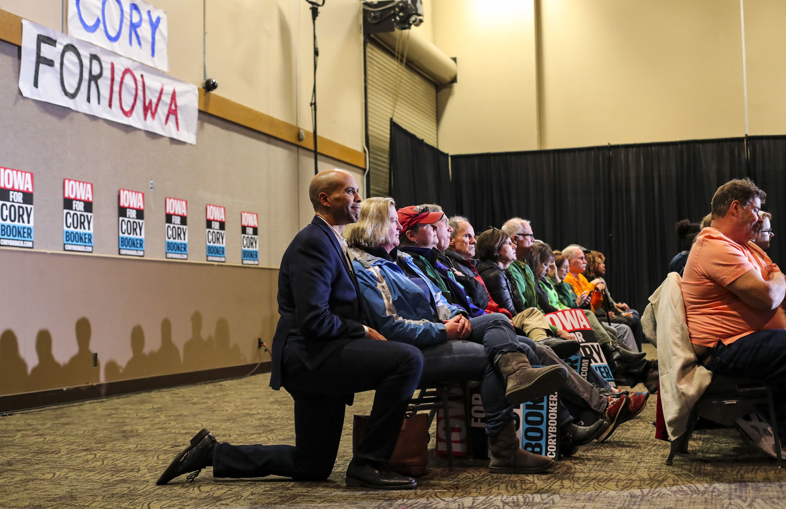 Sen. Cory Booker kneels alongside an attendee sitting in the back row just before he's introduced during a campaign event at the RiverCenter in Davenport, Sunday, March 17, 2019.