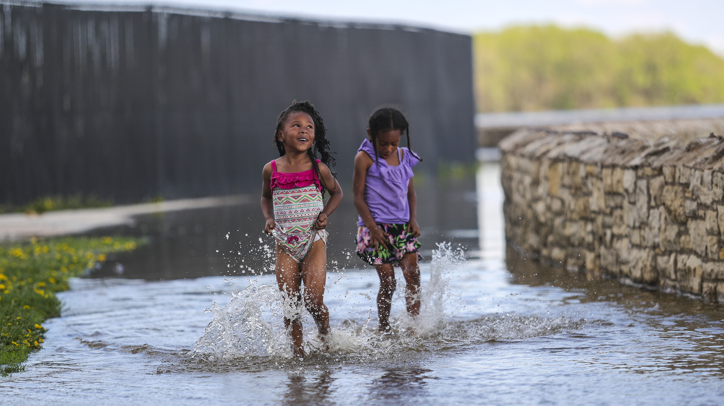 Sisters Queen, 5, left, and Nesse Howard, 4, of Moline play together in shallow flood waters behind Modern Woodmen Park as their dad fishes on the Mississippi riverfront in Davenport, Sunday, May 6, 2018.