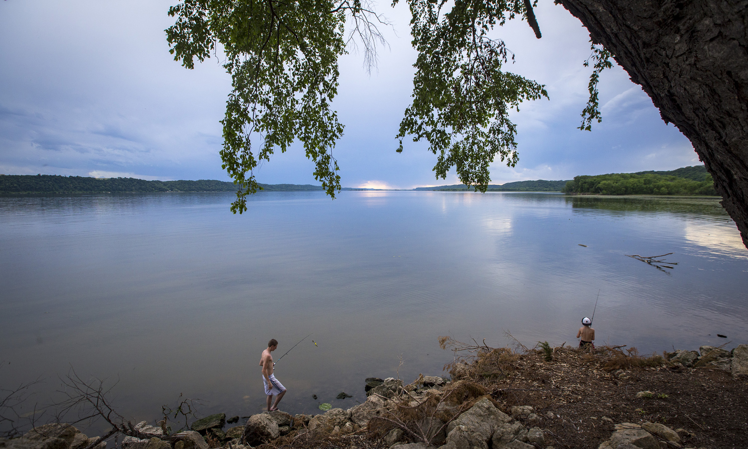Trea Steele, 17, of Gays Mills, Wisconsin walks over toward Tristan Eastlick, 9, of Platteville, Wisconsin while fishing at Grant River Recreation Area in Potosi, Wisconsin, Thursday, June 15, 2017. The boys were camping with family at the campground for the first time and managed to catch a half dozen fish in just about an hour of fishing with worms.