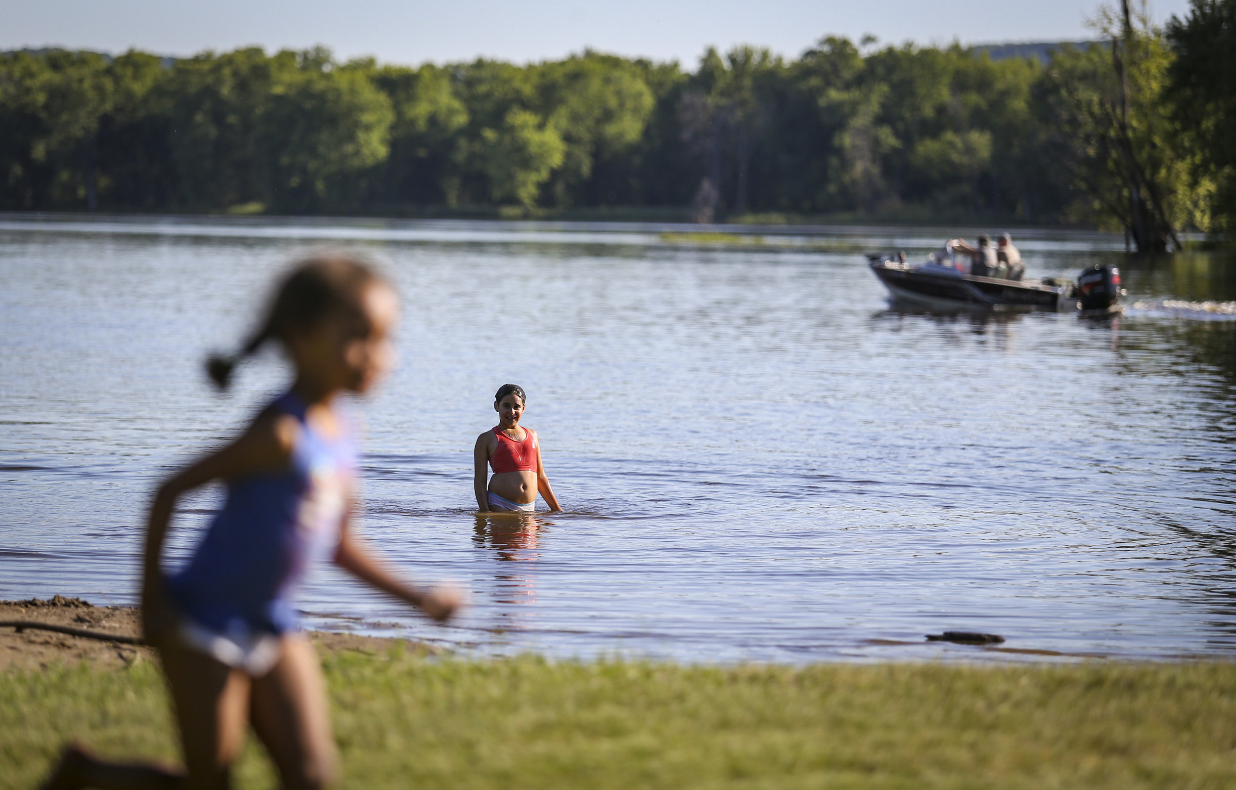 Haley Gonzales, 10, of Lansing, Iowa, looks to her family sitting at a picnic table after showing off a handstand in the Blackhawk Park swimming area in De Soto, Wisconsin, Tuesday, June 6, 2017.