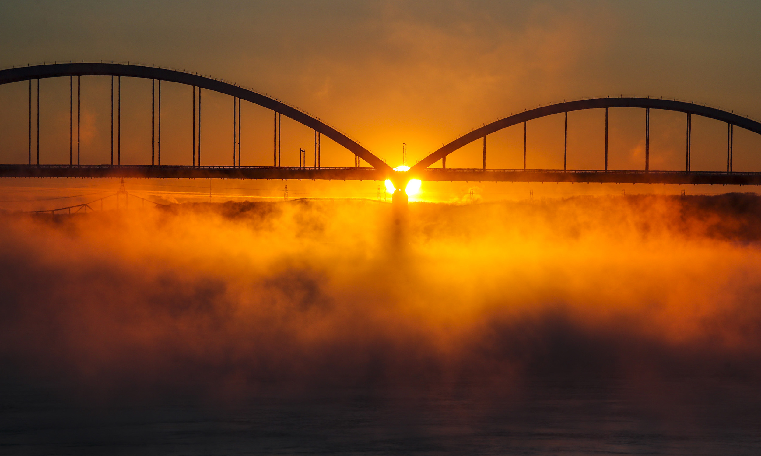 The sun sets behind the Talbot Memorial Bridge as sea fog rises from the Mississippi River in Davenport, Wednesday, Jan. 30, 2019. The Quad-Cities set a record low overnight at 33 degrees below 0 with wind chill reaching as low as -45.