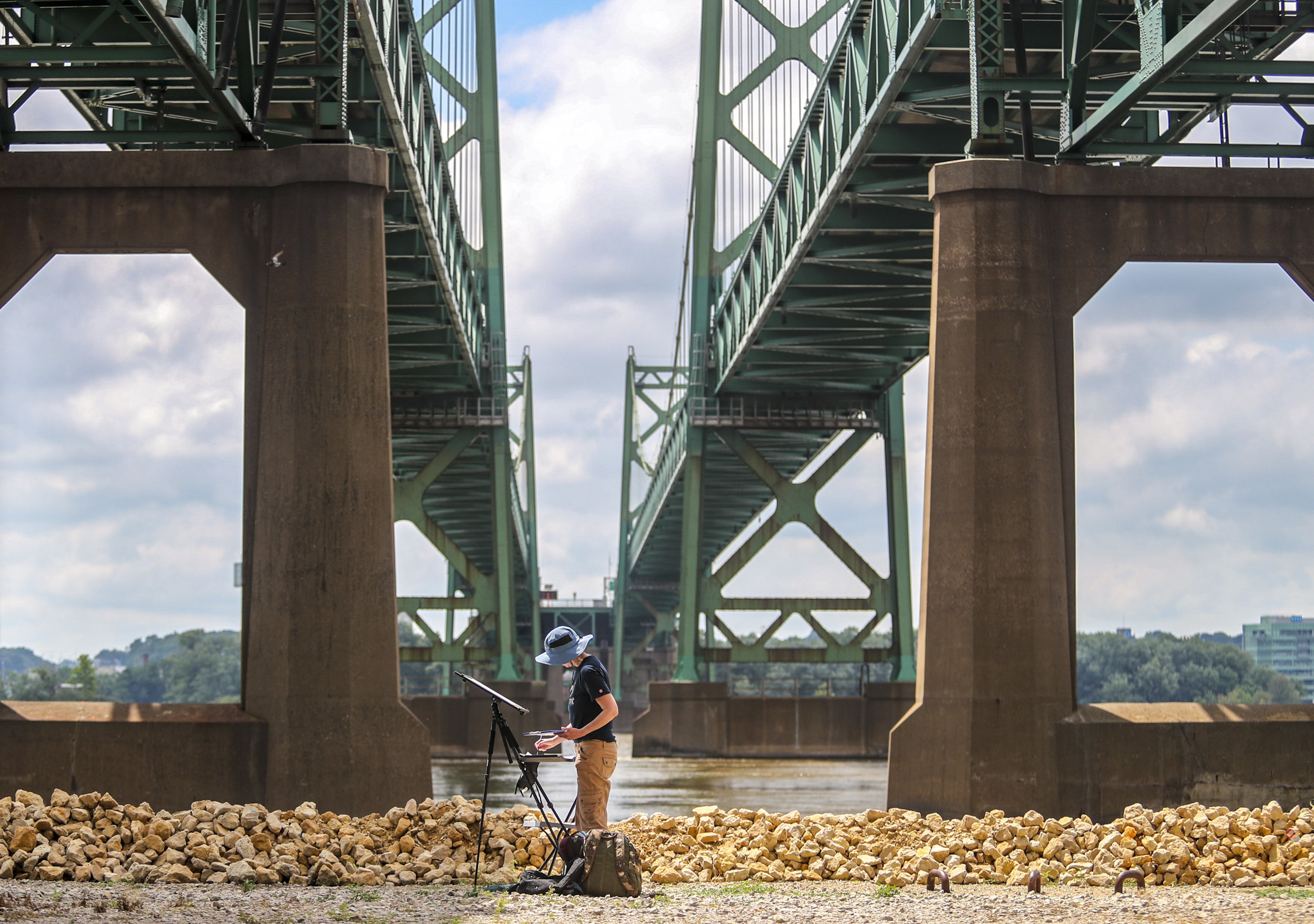 """Victoria Fosmo of Cedar Rapids works on her painting under the Interstate 74 bridge in Bettendorf, Saturday, July 21, 2018. Beréskin Fine Art Gallery and Art Academy hosted the second annual """"Plein Air Paint Out"""" event inviting around 30 artists to come out and paint on the bike path between Leach Park and the gallery at 2967 State Street between 8 a.m. and 4 p.m. before a showcase of the finished art at the gallery in the evening."""