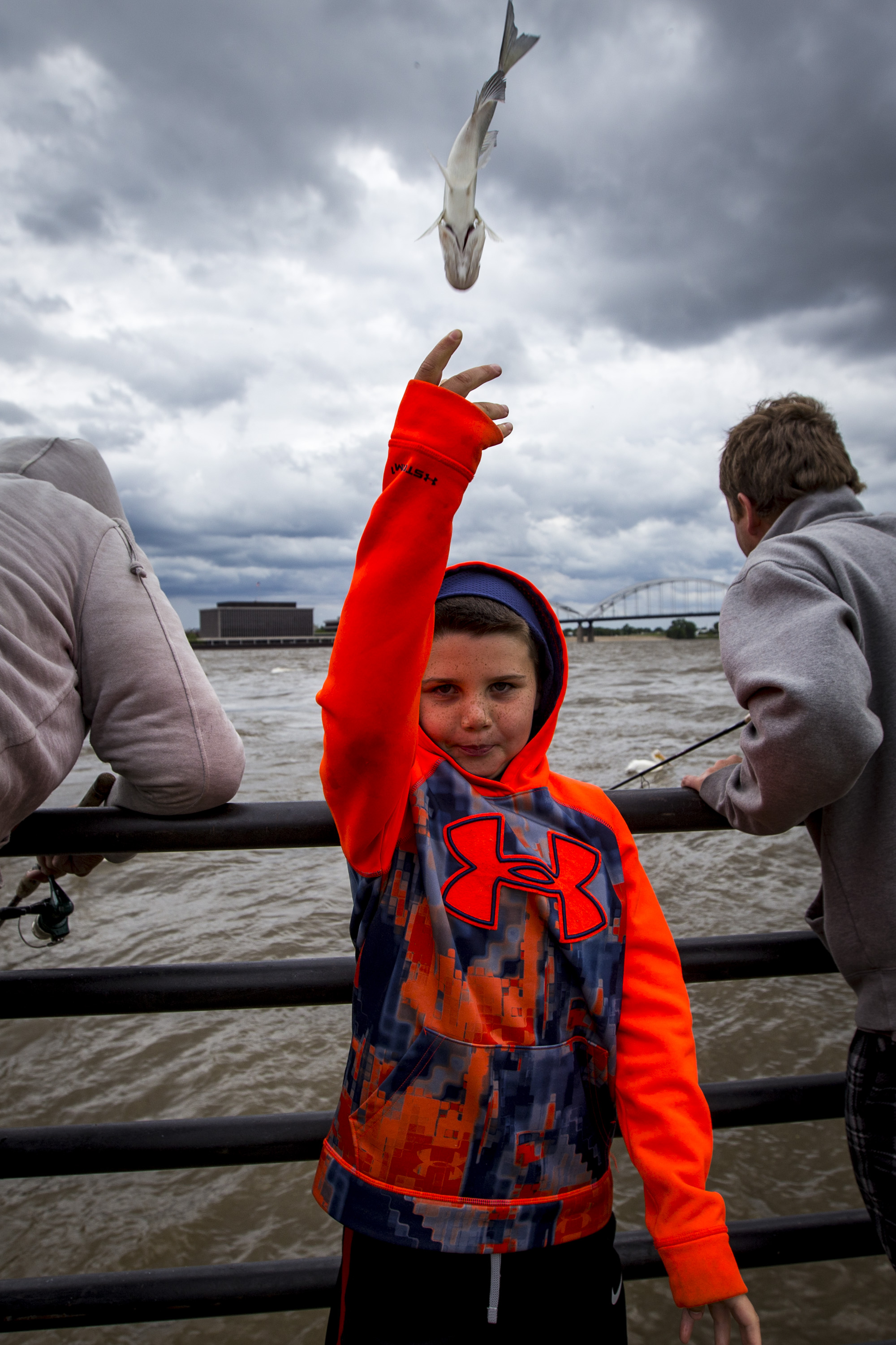 Anthony Harvey, 9, of Davenport tosses a small fish caught by one of the men back into the river, having deemed it too small to keep, at the old Rhythm City Casino site in Davenport, Monday, May 22, 2017.