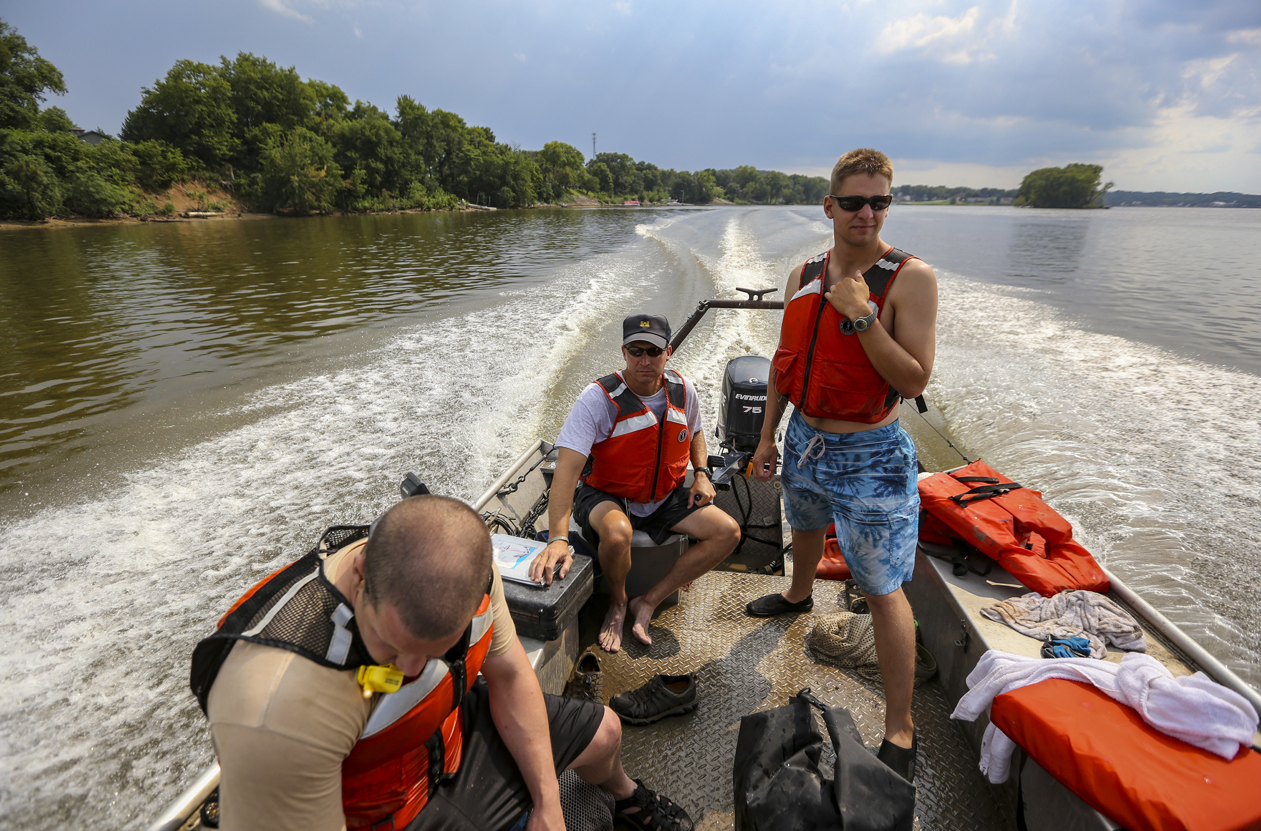 St. Paul District Army Corp of Engineers biologist Dan Kelner drives the boat as St. Paul District Army Corps of Engineers Fisheries biologist Trevor Cyphers, right, and Rock Island district biologist Kjetil Henderson prepare to relocate counted mussels as a part of a survey in the Mississippi River in Cordova, Illinois, Wednesday, August 2, 2017. On the first Wednesday of August each year, around 70 workers get together representing 11 different corporations, universities and other agencies to check the status of endangered mussel species. Information about the trends of the mussels can be used to infer trends of the river. Due to mussel diversity in the area, Cordova offers a rare sampling proving valuable for research.