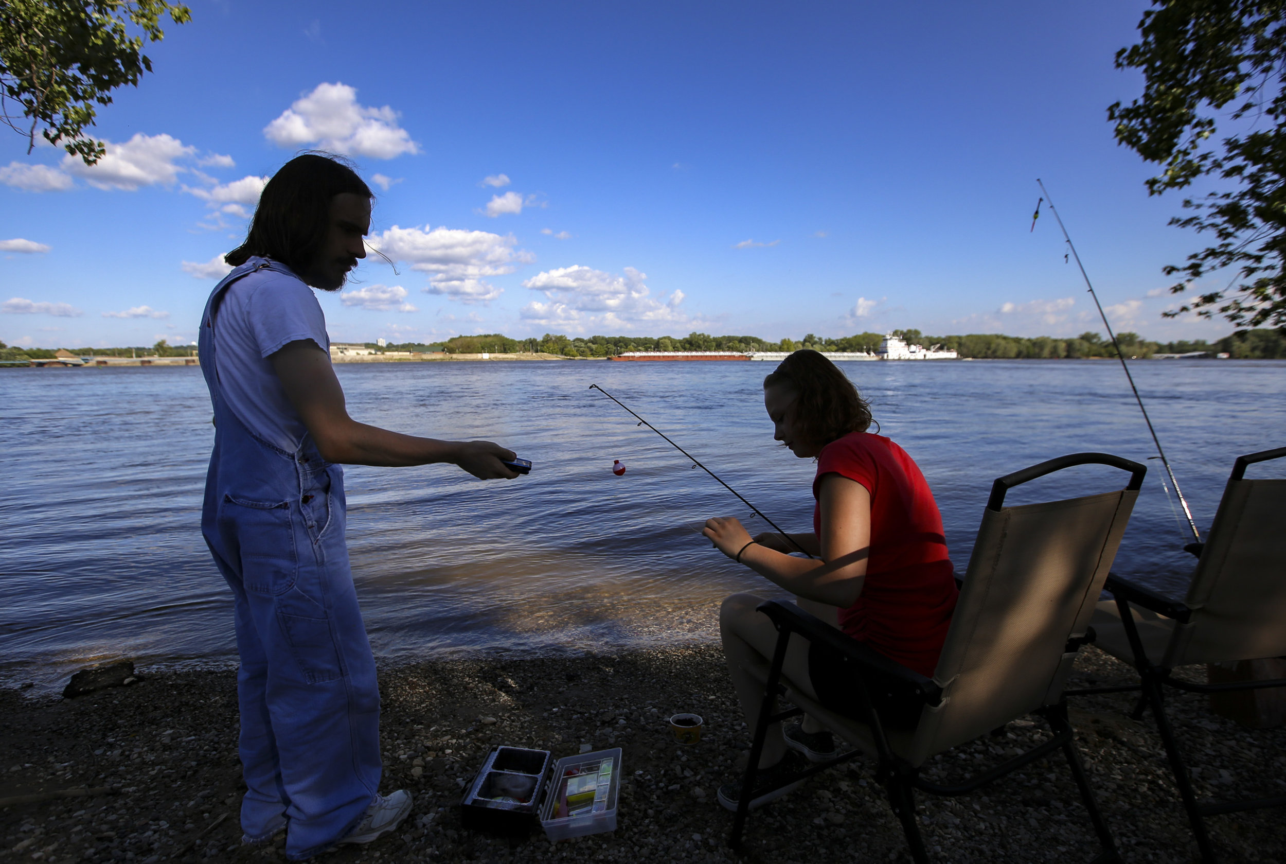 Alexandria Bribriesco of Davenport turns back to make a joke with Taylor Lance of Bluegrass as he baits his hook along the Mississippi River on Credit Island in Davenport, Tuesday, July 24, 2018. The two attended Mid-City High School together, graduating in 2017, and had not seen one another for about a year until Bribriesco reached out to Taylor to tell him they were going fishing.
