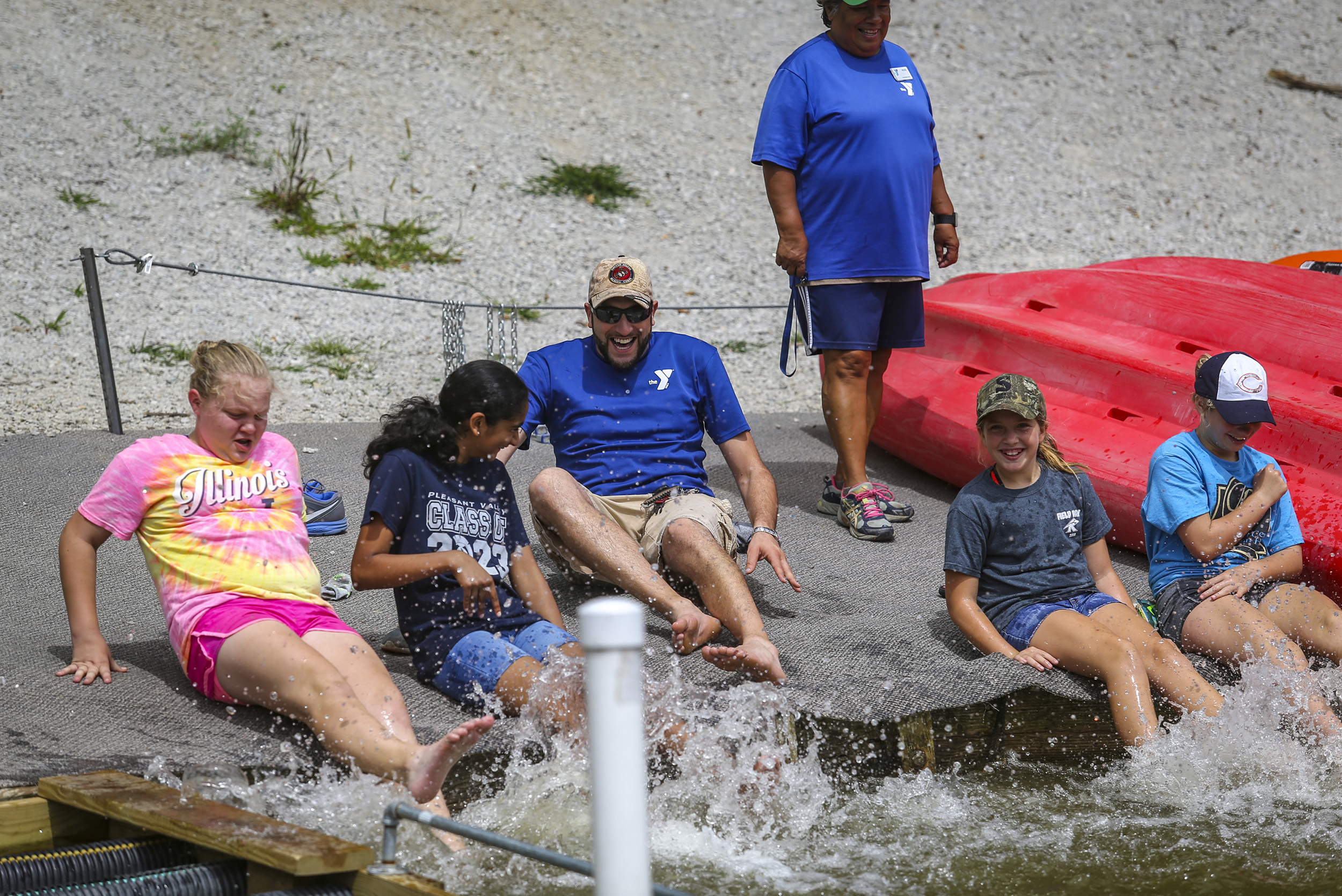 YMCA campers Haley Hotchkiss, 12, left, Julianne Binto, 11, Kylee White, 12, and Lilly Elliot, 12, try to kick and splash water on Rock Island Program Coordinator Rich Yerington during their lunch break at Lake George in Illinois City, Illinois, Thursday, August 17, 2017.