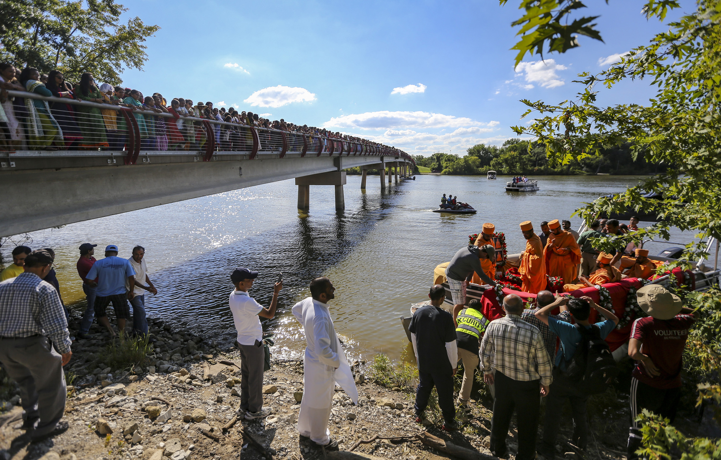 """Hundreds of Hindu followers watch as a group of swamis load onto a pontoon boat to perform a ceremony on the Mississippi River at Credit Island in Davenport, Sunday, July 30, 2017. A Hindu ceremony was held in honor of His Holiness Pramukh Swami Maharaj, who passed away about a year ago, by his followers from the region. Maharaj was the guru and """"pramukh"""" or president of the Bochasanwasi Shri Akshar Purushottam Swaminarayan (BAPS,) an international socio-spiritual Hindu organization."""