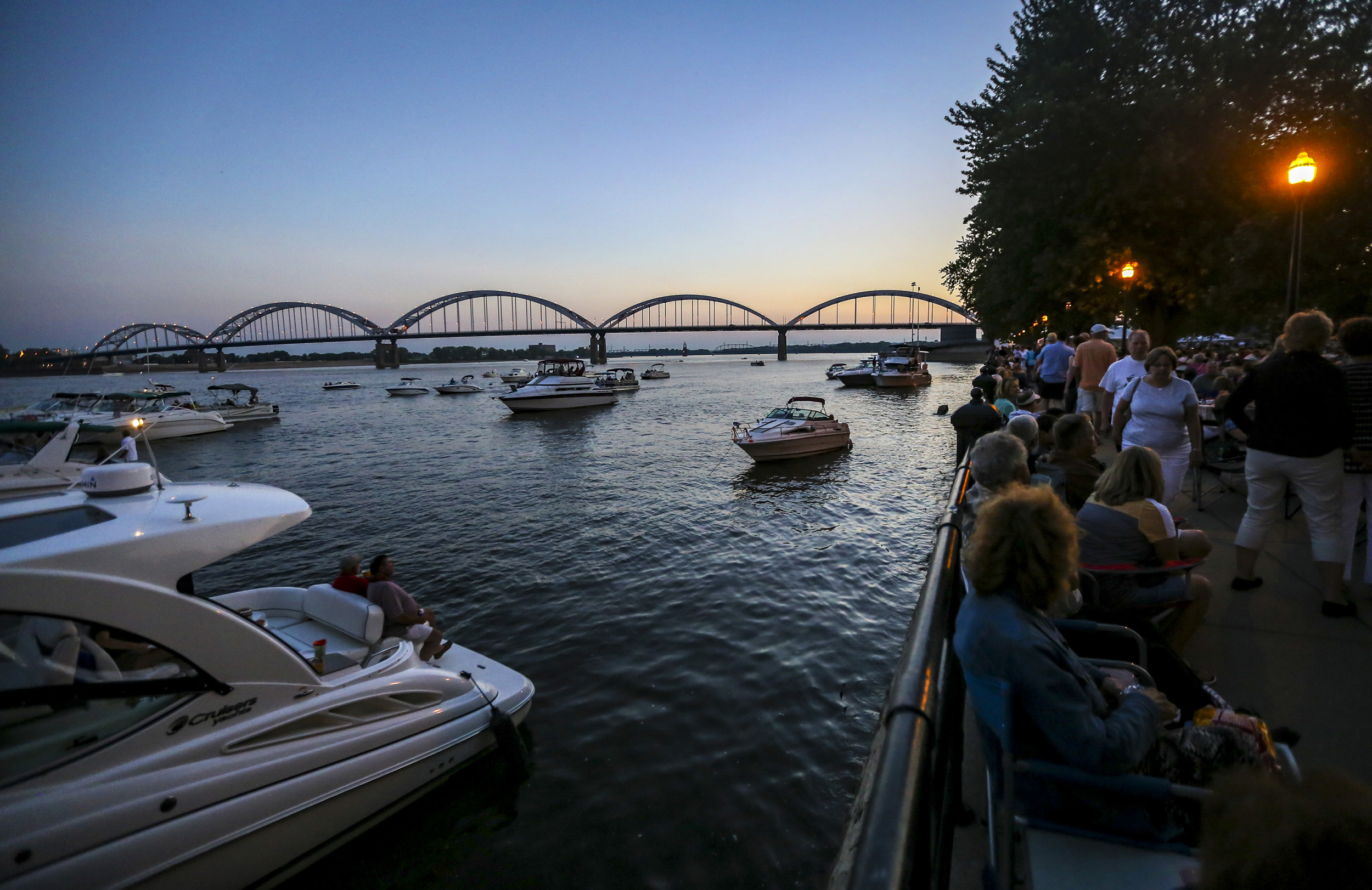 Attendees walk up the riverfront path as boaters listen to the performance from the Mississippi River at LeClaire Park in Davenport, Saturday, August 19, 2017. The Quad-City Bank & Trust Riverfront Pops: The Beatles' Greatest Hits show was performed by the Quad-City Symphony Orchestra and was enjoyed by thousands in the park as well as on the river.