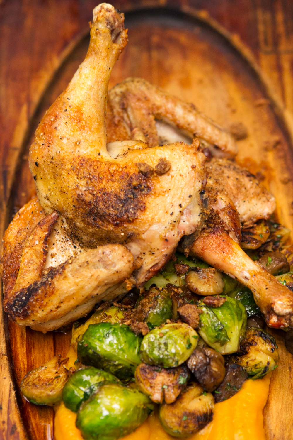 Roasted half chicken with glazed brussel sprouts and sweet potato puree.