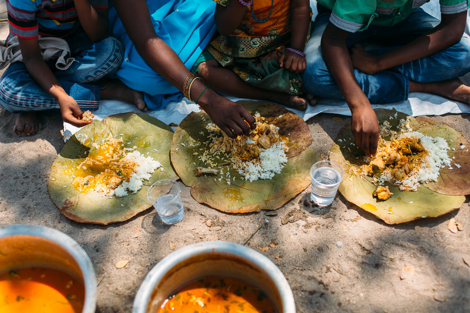 Families eat the chicken and spicy rice together in Vettuvanam, India on March 11, 2016.