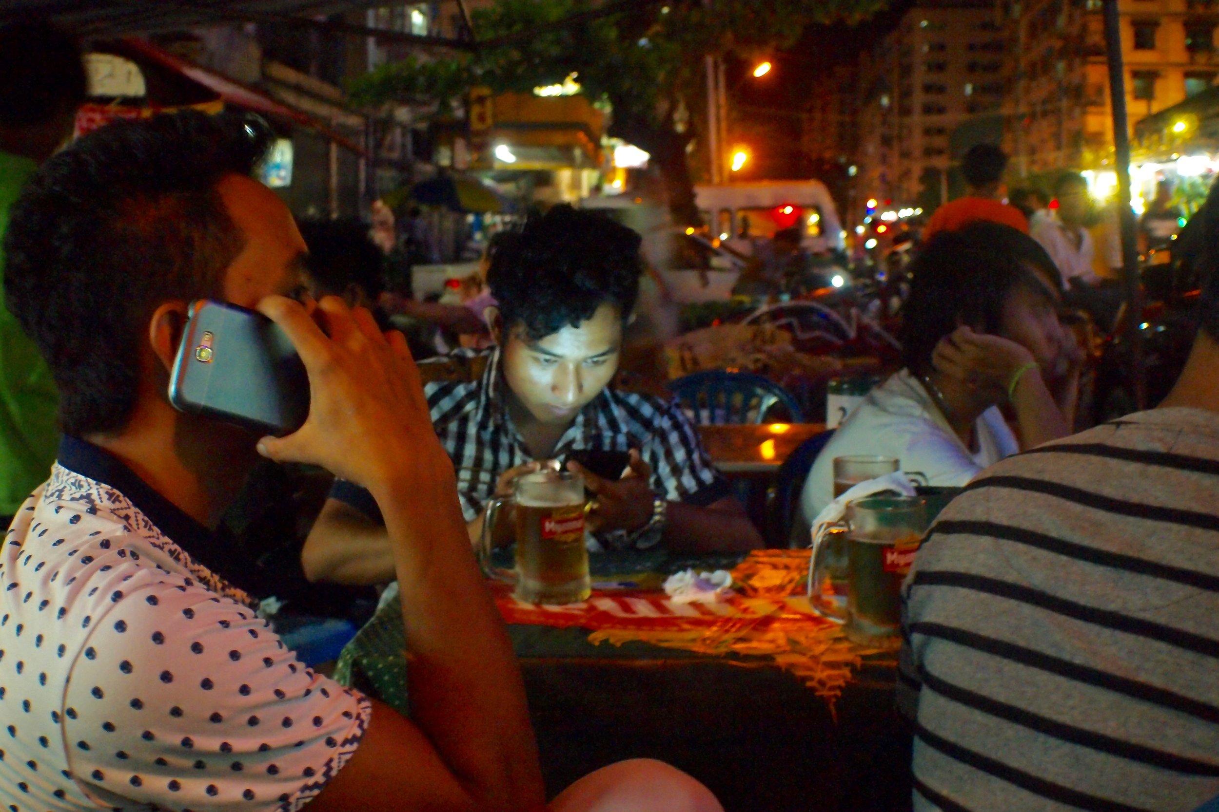 Smartphone users on a street in Yangon, Myanmar. (C) Remko Tanis
