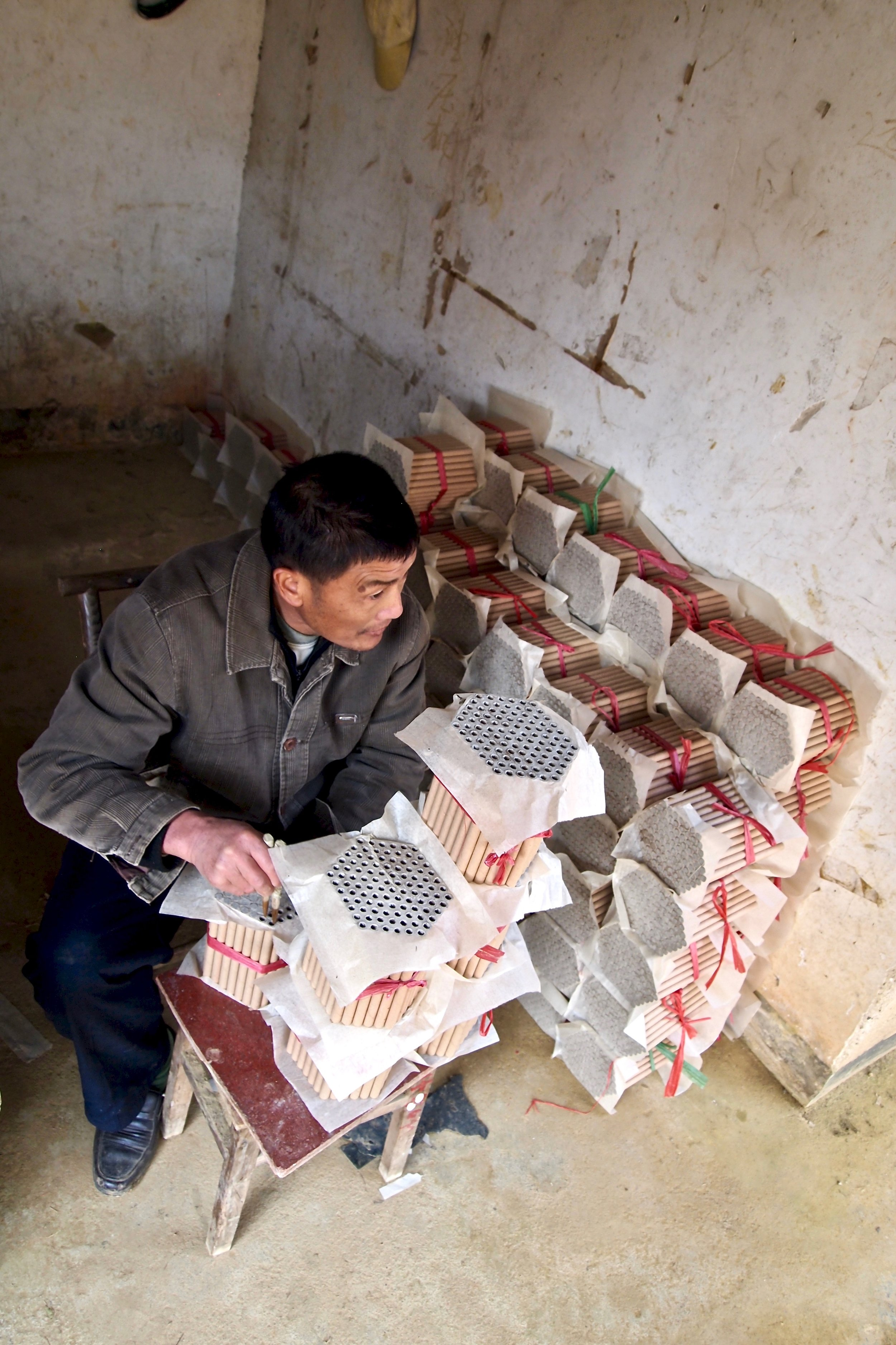 An employee of Dream Fireworks in Liuyang, China measuring powdered dynamite. Photo: (C) Remko Tanis