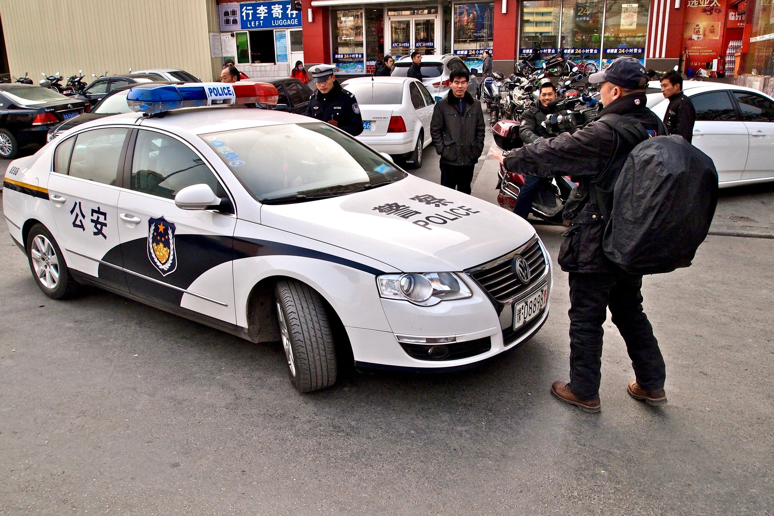 Lu Jianfu filming an illegally parked police car in Zhengzhou, China. Photo: (C) Remko Tanis