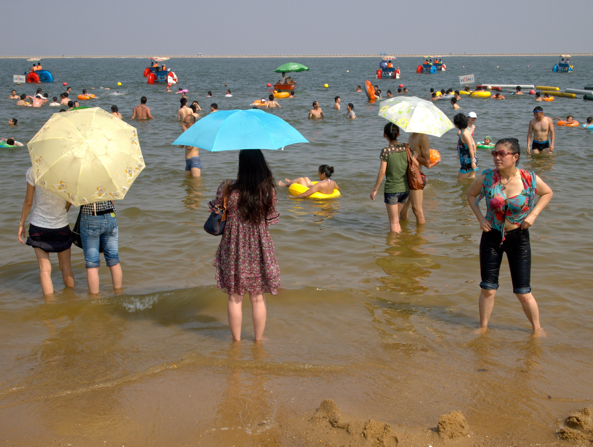 People carrying umbrellas to protect their skin from the sun at Jinshan City Beach, Shanghai, China. Photo: (C) Remko Tanis