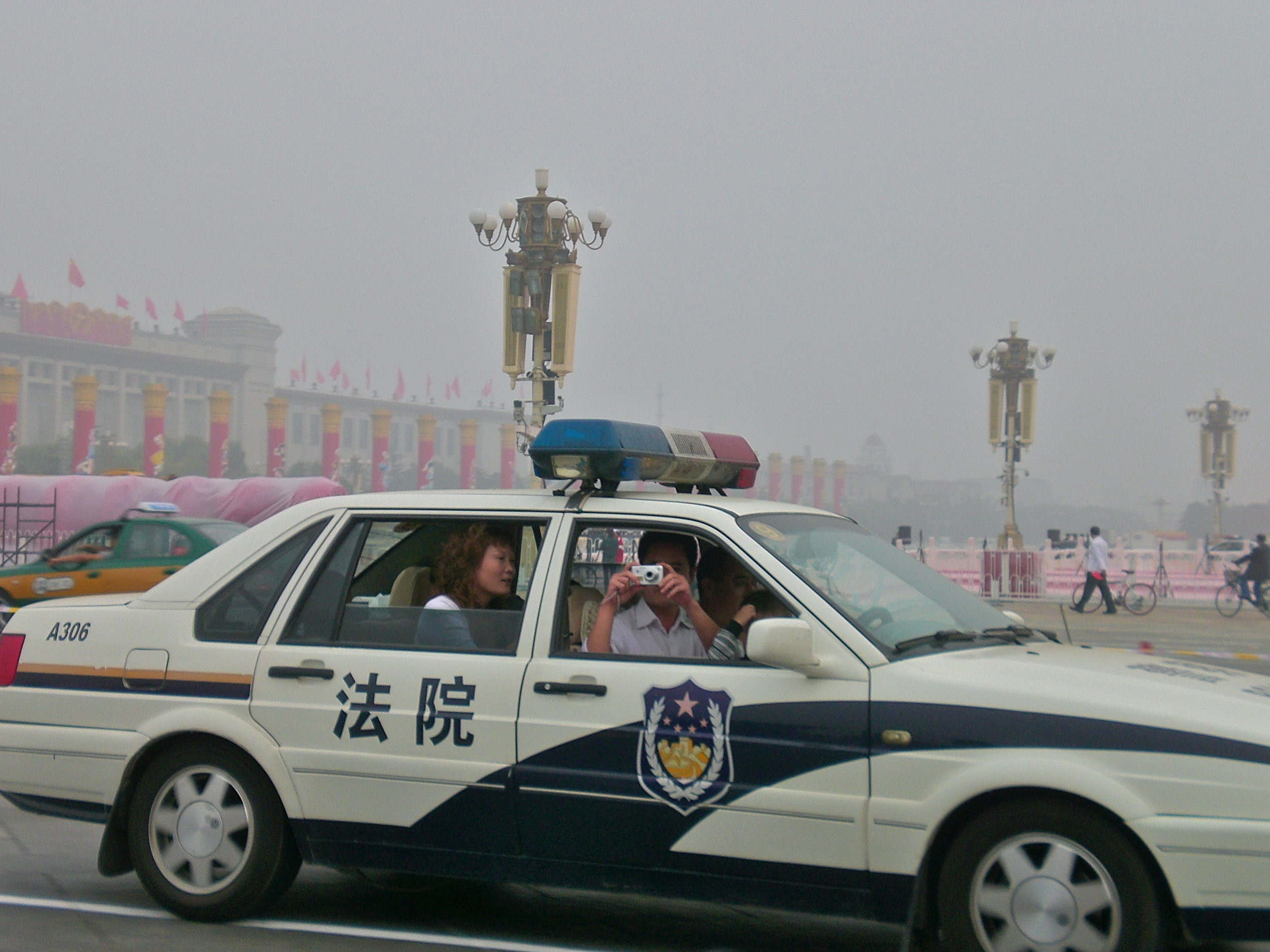 A police man taking photos from a patrol car on Tiananmen Square, Beijing, China. Photo: (C) Remko Tanis