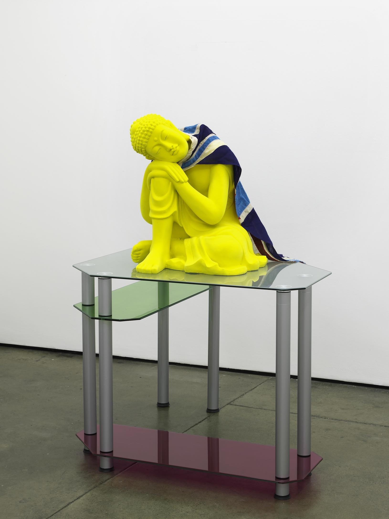 Matthew Darbyshire Untitled Homeware No. 13, 2011 yellow flocked buddha statue, turquoise flocked vintage union jack flag, coloured glass gels, glass and steel support 135 x 98 x 98 cm