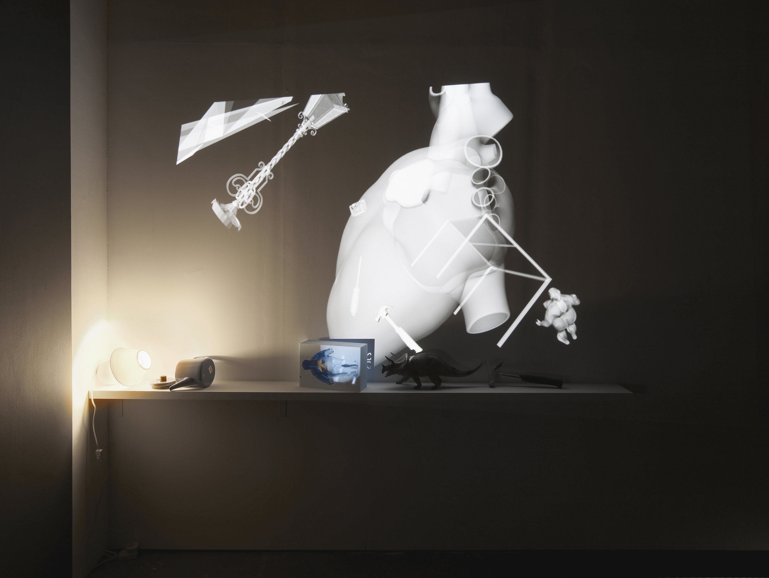 Christina Mackie  Fall Force (Installation)  2012/2017  Stereo vision projection, blu-ray disc, 3D glasses, 3D projector, sofa, teapot, hammer, plastic dinosaur, foam woman and lamp  Dimensions variable
