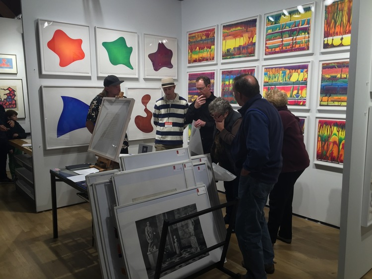 James Stroud at the 2015 E/AB fair in New York City. Markus Linnenbrink's EVENTHOUGHYOUHAVETOGO monotypes hang from the back wall.