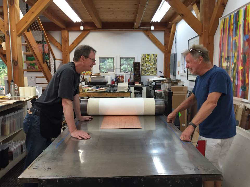 James Stroud (left) and Roger Tibbetts (right), prepare Tibbett's plate on the press for printing.