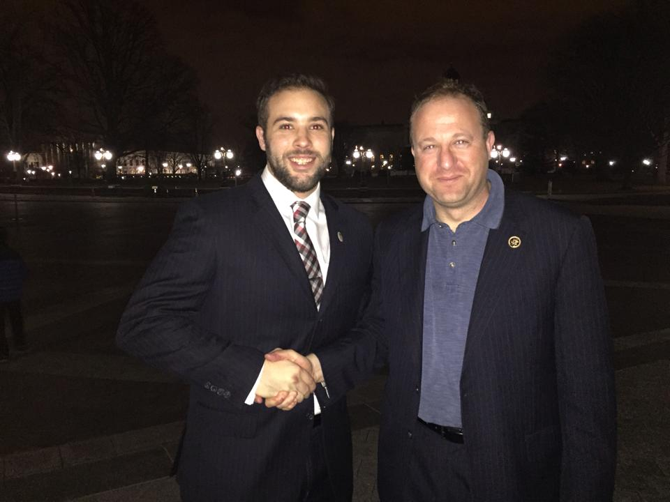 GW Veteran, Tyler McManus, passes a GW Veterans Challenge Coin to Congressman Jared Polis, 2nd district of Colorado, as a thank you for giving GW Veterans a tour of the Capitol.