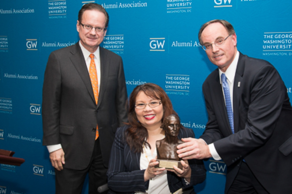 GW Alumni Association President Steve Frenkil, right, and Elliott School of International Affairs Dean Michael Brown present the Distinguished Alumni Achievement Award to Rep. Tammy Duckworth.