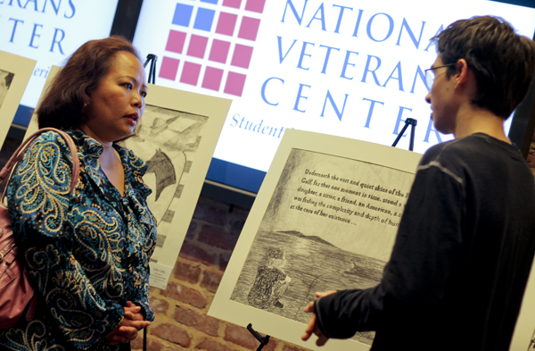 Alumnus and veteran Melanie Alvarez listens to a Maryland high school student Max Maynard discuss the artwork he created to depict her military service.