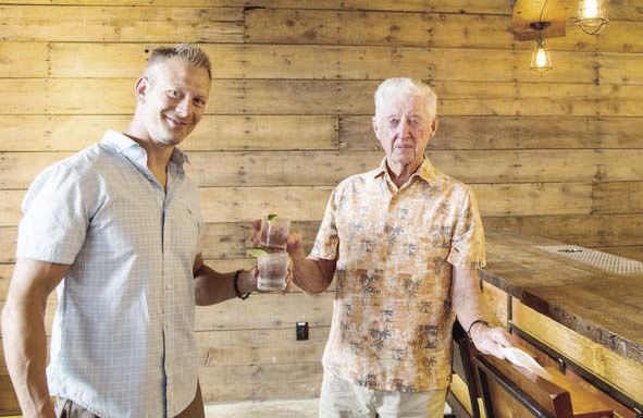 Jeremiah Logemann and Ron Nordeng check out the distillery made of wood repurposed from the Nordeng family barn.