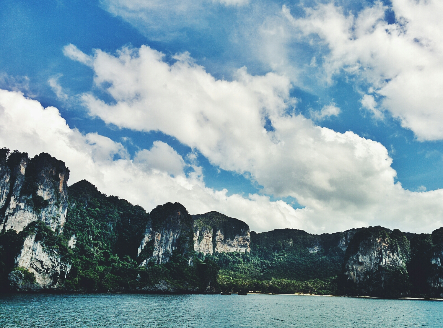 The fleeting clouds passing over the illusive permanence of the sheer cliffs of Railay Beach, Thailand.