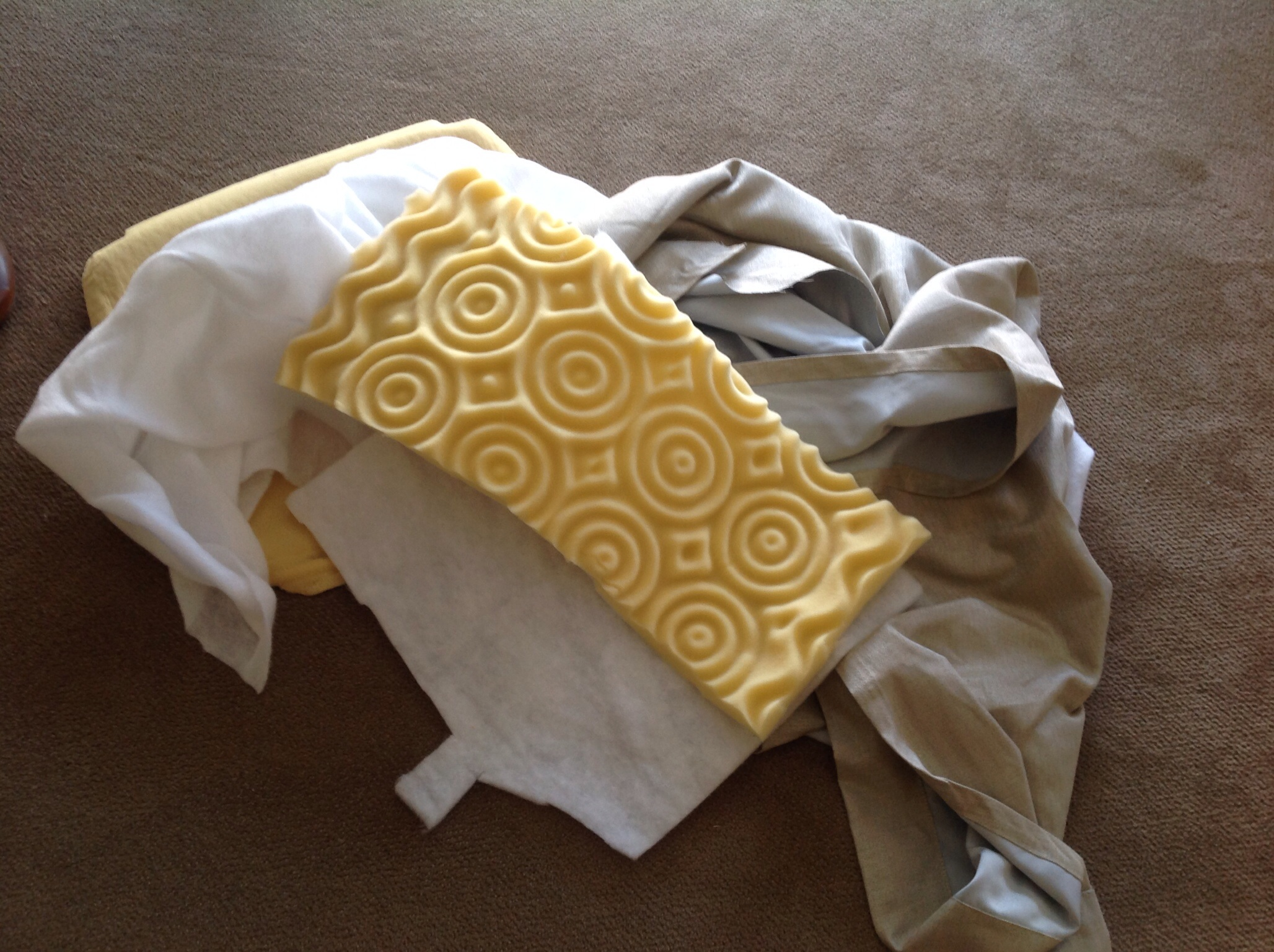 """The seat bottom needed some extra support so I went into my stash. I added the yellow waffle cushion first, covered it in batting then wrapped the entire thing with fabric. I used a staple gun and stapled about every 1/2""""."""