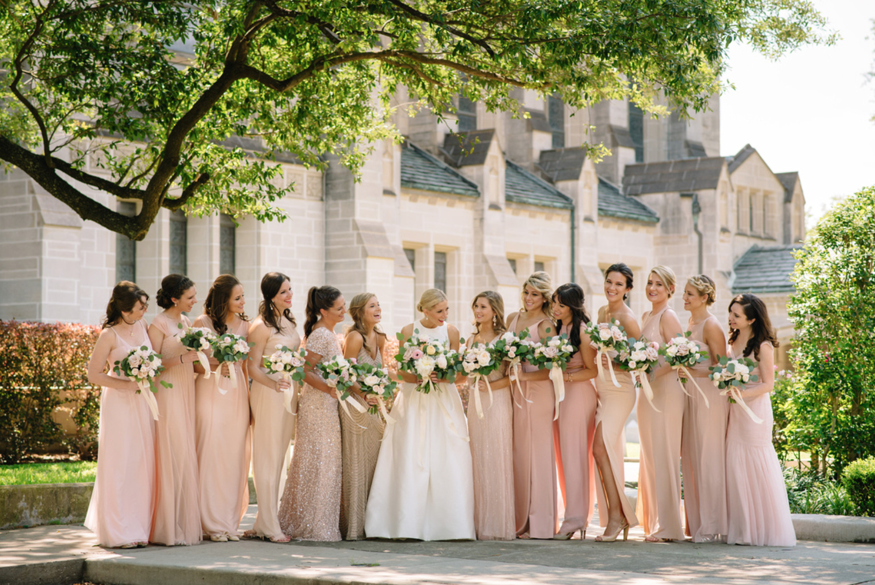 13 beautiful bridesmaids in blush colored dresses with bouquets by Maxit Flower Design in Houston, TX.