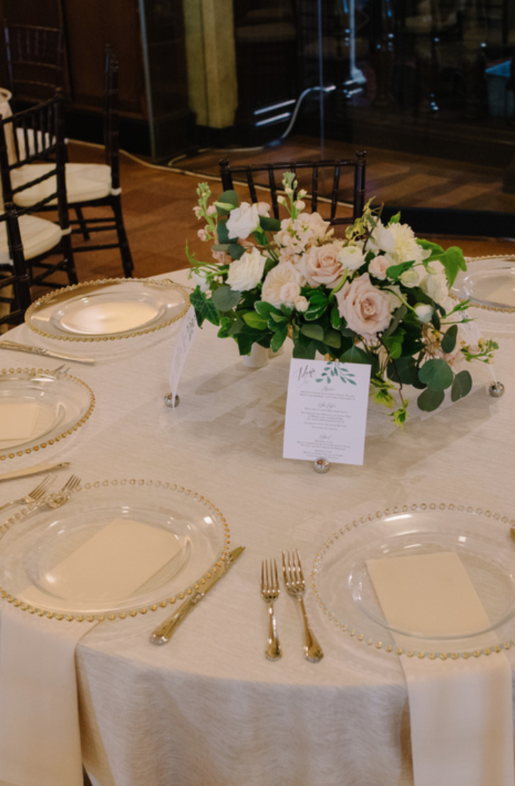 A compote arrangement used for centerpieces at this gold and blush wedding.