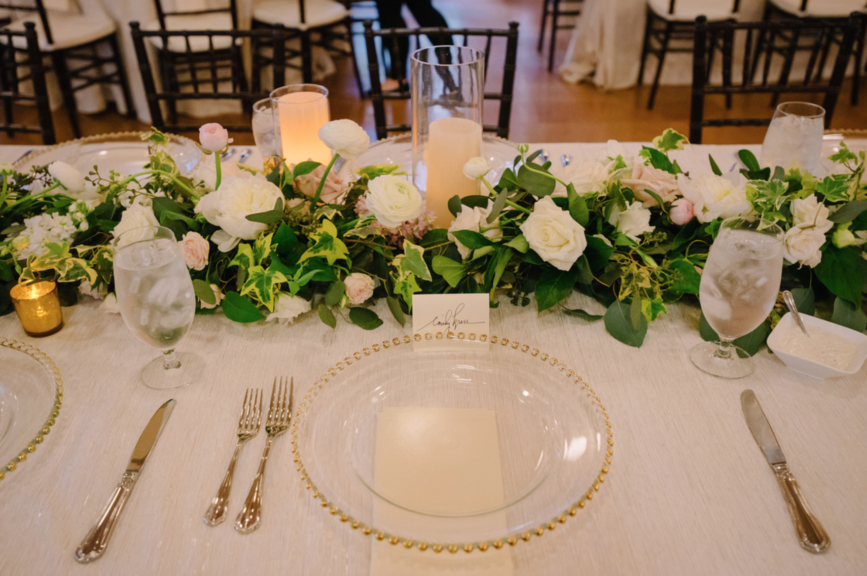 Floral garland is the focus on this gold toned head table.