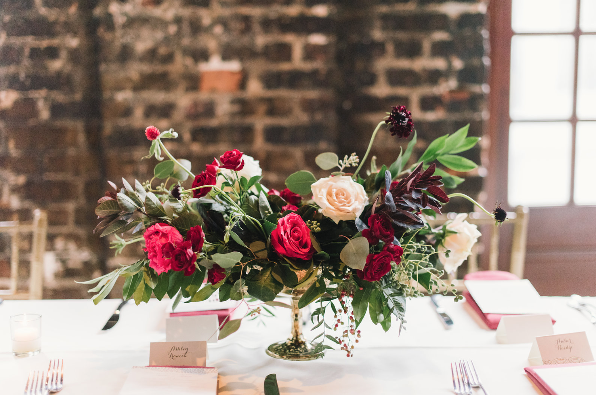 A close-up of the compote arrangement featuring roses and greenery. Florals by Maxit Flower Design. Red based floral arrangements.