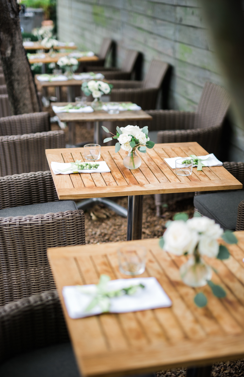 Outdoor seating with white flower bud vases.