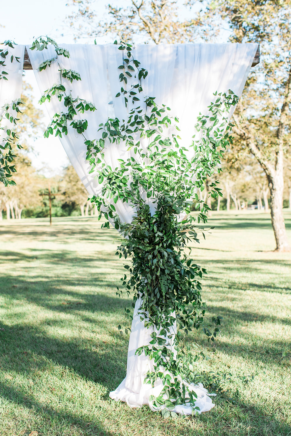Ceremony site with draping covered in greenery.