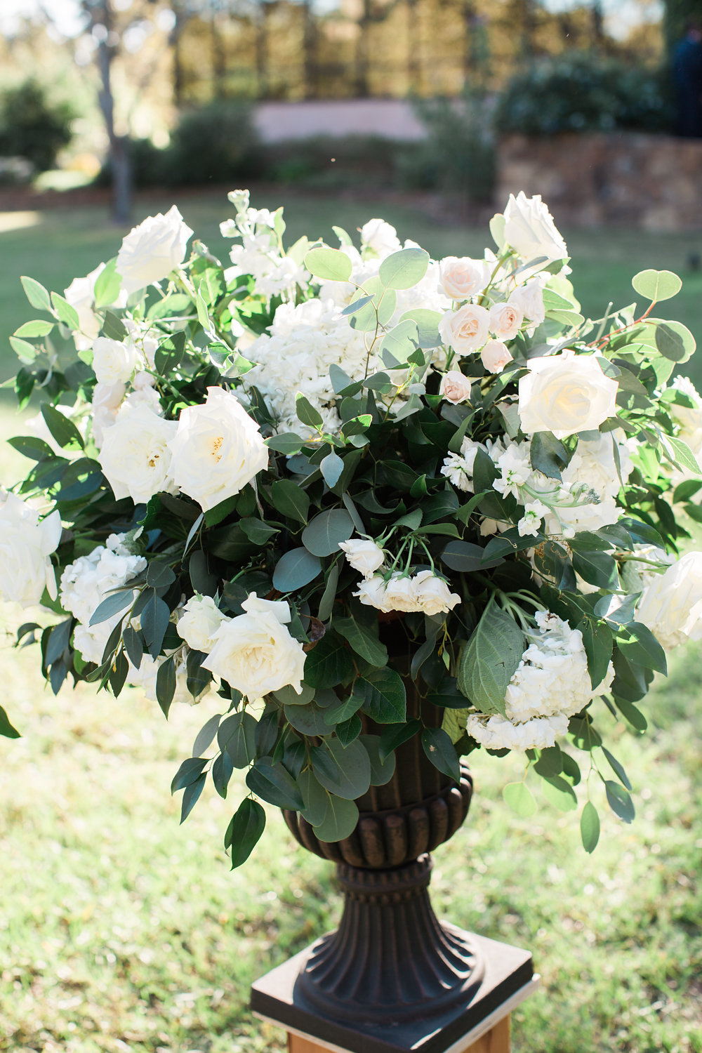 Large urn arrangement featuring roses and greenery.