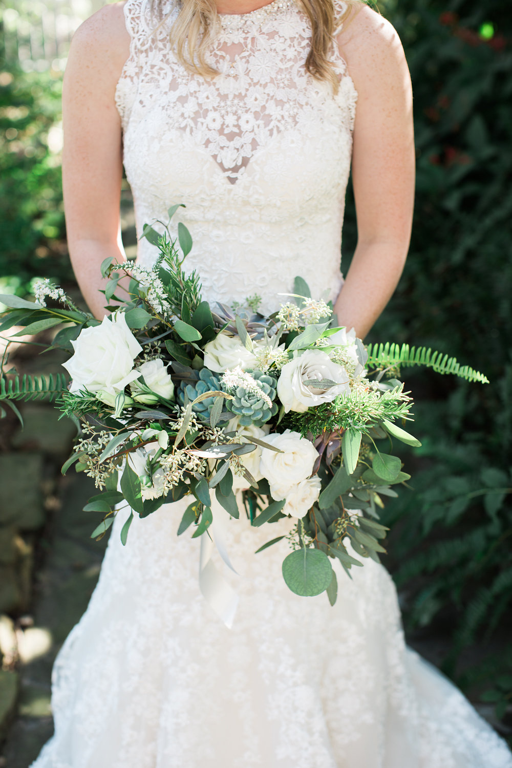 Danni holding her bouquet made with roses, greenery and succulents.