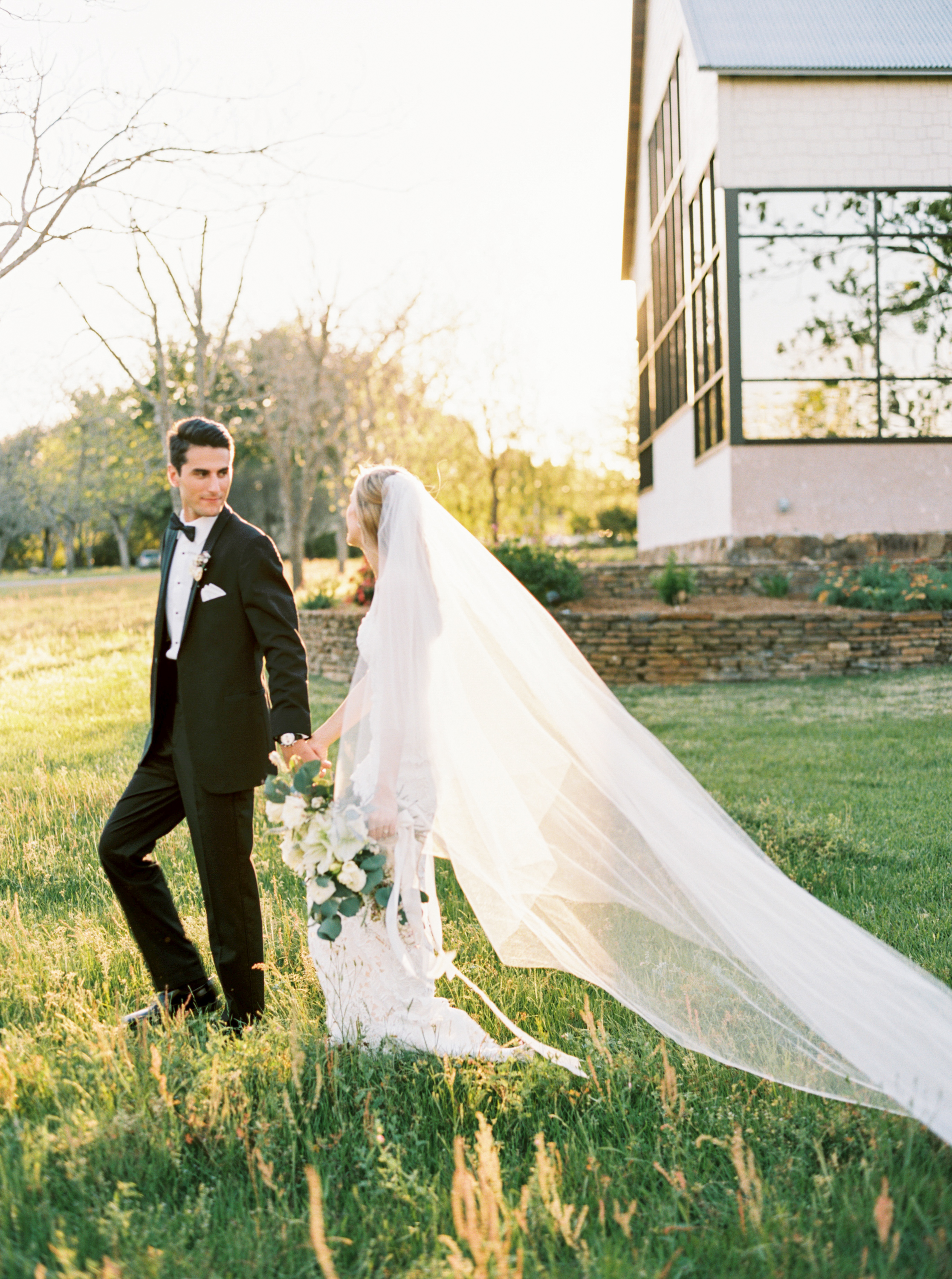 bride and groom at chandelier grove flowers by maxit flower design